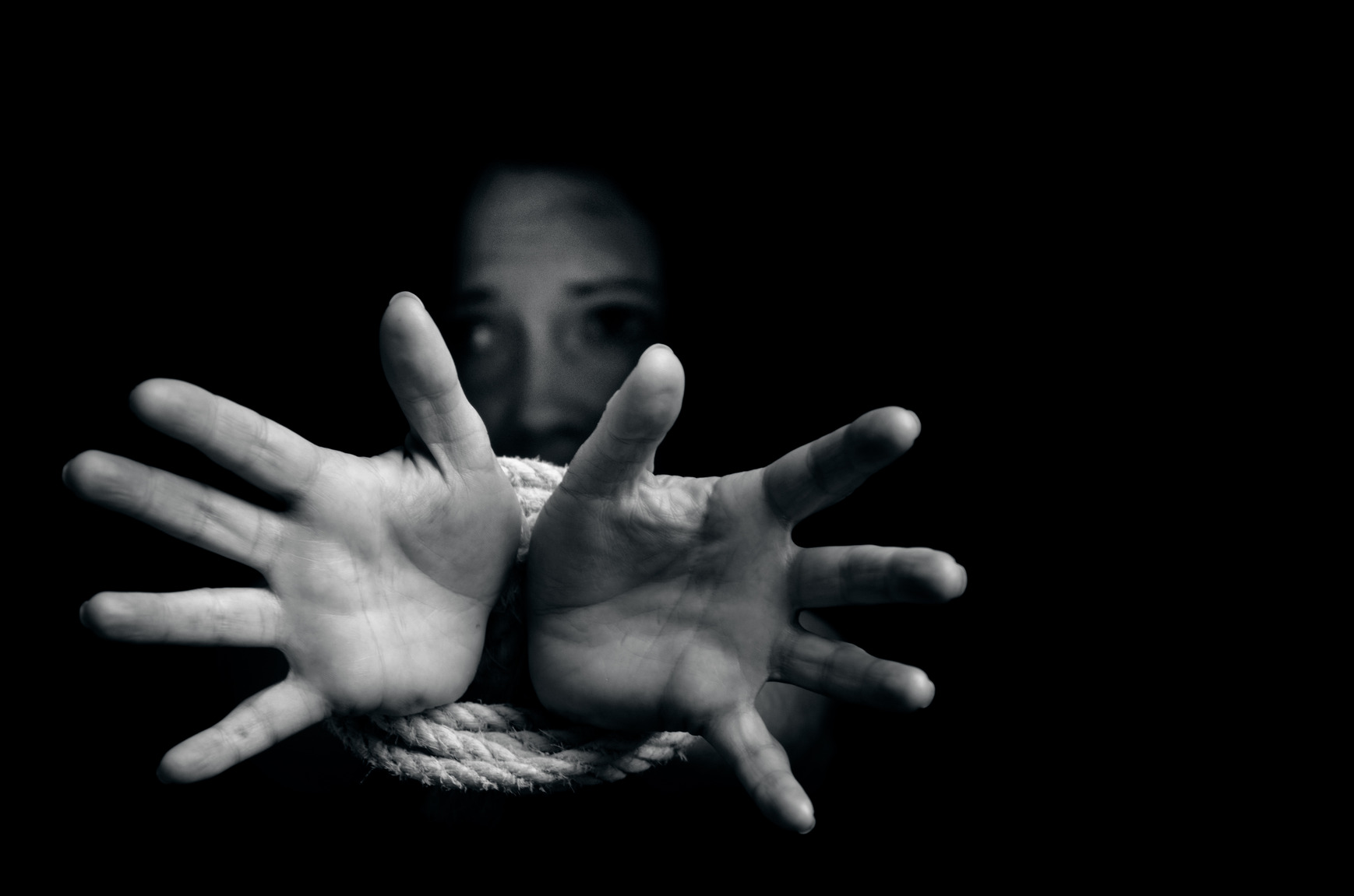 Woman with hands tied up with rope in emotional stress and pain